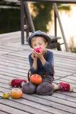 Vrolijke jongenszitting met pompoenen en appelen Stock Afbeeldingen