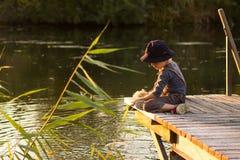 Vrolijke jongenszitting met stokken in handen Royalty-vrije Stock Foto's