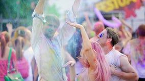Vrolijke jongeren die kleurrijk poeder in lucht werpen, die bij festival dansen stock video