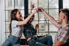 Vrolijke jongeren die met glazen wijn en het kijken toejuichen stock afbeeldingen
