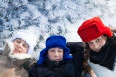 Vrolijke jongeren die pret op sneeuw met ijsachtergrond hebben tijdens Kerstmisvakantie met exemplaarruimte Stock Fotografie