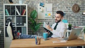 Vrolijke kerel die aan muziek door oortelefoons luisteren die in notitieboekje op het werk schrijven stock video