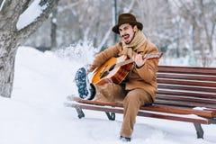 Vrolijke kerel het spelen gitaar in park in de winter Royalty-vrije Stock Fotografie