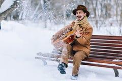 Vrolijke kerel het spelen gitaar in park in de winter Stock Fotografie