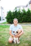 Vrolijke kerel op een gang in het park op een de zomerdag met zijn hond Jack Russell Zij zijn volledig van vreugde, glimlachen en stock afbeeldingen