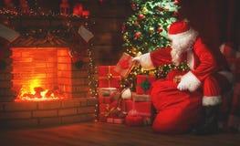 Vrolijke Kerstmis! de Kerstman dichtbij de open haard en boom met gi stock foto's