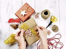 Vrolijke Kerstmis - de vrouw overhandigt verpakkende giftdoos en decoratie Stock Afbeelding