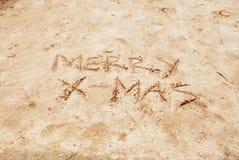 Vrolijke Kerstmis die op strandzand wordt geschreven Royalty-vrije Stock Afbeeldingen