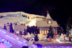 Vrolijke Kerstmis en dorpsscène met kerk Stock Afbeeldingen