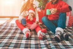 Vrolijke Kerstmis en Gelukkig Nieuwjaar Besnoeiingsmening van familiezitting samen op deken Zij dragen kleurrijke kleren mens en stock afbeelding