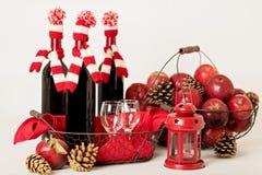Vrolijke Kerstmis en Gelukkig Nieuwjaar Flessen wijn in gebreid Stock Foto's