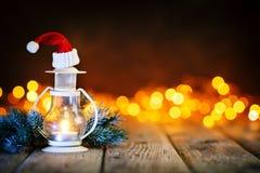 Vrolijke Kerstmis en Gelukkig Nieuwjaar Kaars en Kerstmisspeelgoed op een houten lijst aangaande de achtergrond van een slinger B stock afbeeldingen
