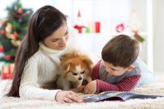 Vrolijke Kerstmis en Gelukkig Nieuwjaar Mamma die een boek thuis lezen aan haar leuke zoon dichtbij Kerstboom stock foto