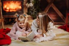 Vrolijke Kerstmis en Gelukkig Nieuwjaar Mooie familie in Kerstmisbinnenland Vrij jonge moeder die een boek lezen aan haar stock afbeeldingen