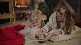 Vrolijke Kerstmis en Gelukkig Nieuwjaar Mooie familie in Kerstmisbinnenland Vrij jonge moeder die een boek lezen aan haar stock videobeelden