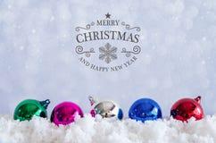 Vrolijke Kerstmis en gelukkige nieuwe jaartekst met decoratieballen Stock Afbeelding