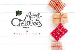Vrolijke Kerstmis en Gelukkige Nieuwjaartekst met giftvakjes op wit stock afbeeldingen