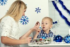 Vrolijke Kerstmis en gelukkige vakantie! De moeder en de zoon verfraaien de denneappel met schitteren De familie creeert decorati stock afbeelding