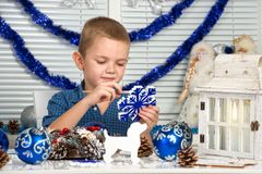 Vrolijke Kerstmis en gelukkige vakantie! Een jongen die een sneeuwvlok schilderen Het kind creeert decoratie voor Kerstmisbinnenl stock afbeelding