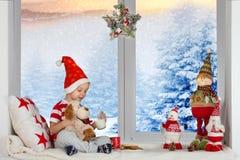 Vrolijke Kerstmis en gelukkige vakantie! Een kleine jongen zit en speelt met een stuk speelgoed melk en de koekjes van het hondvo stock foto
