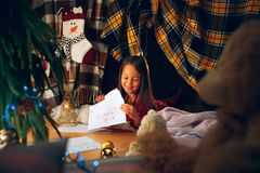 Vrolijke Kerstmis en gelukkige vakantie Leuk schrijft weinig kindmeisje de brief aan Santa Claus dichtbij Kerstboom royalty-vrije stock afbeelding