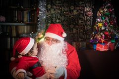 Vrolijke Kerstmis en gelukkige vakantie! Leuk weinig van kindmeisje en Santa Claus zittings dichtbij gloeiende spar royalty-vrije stock foto