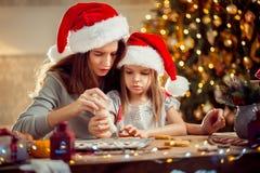 Vrolijke Kerstmis en gelukkige vakantie Moeder en dochter kokende Kerstmiskoekjes stock fotografie