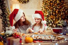 Vrolijke Kerstmis en gelukkige vakantie Moeder en dochter kokende Kerstmiskoekjes royalty-vrije stock afbeeldingen