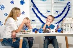 Vrolijke Kerstmis en gelukkige vakantie! Moeder en twee zonen die een sneeuwvlok schilderen De familie creeert decoratie voor Ker stock afbeeldingen