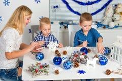 Vrolijke Kerstmis en gelukkige vakantie! Moeder en twee zonen die een sneeuwvlok schilderen De familie creeert decoratie voor Ker royalty-vrije stock afbeelding