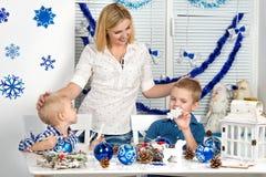 Vrolijke Kerstmis en gelukkige vakantie! Moeder en twee zonen die een sneeuwvlok schilderen De familie creeert decoratie voor Ker royalty-vrije stock foto