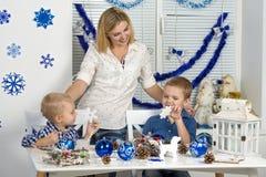 Vrolijke Kerstmis en gelukkige vakantie! Moeder en twee zonen die een sneeuwvlok schilderen De familie creeert decoratie voor Ker stock afbeelding
