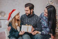 Vrolijke Kerstmis en Gelukkige Vakantie Vrolijke Moeder, vader en haar leuk dochtermeisje die giften ruilen Ouder en Royalty-vrije Stock Afbeeldingen