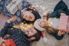 Vrolijke Kerstmis en Gelukkige Vakantie Vrolijke Moeder, vader en haar leuk dochtermeisje die giften ruilen Ouder en Stock Afbeeldingen