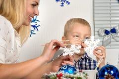 Vrolijke Kerstmis en gelukkige vakantie! Moeder en zoon die een sneeuwvlok schilderen De familie creeert decoratie voor Kerstmisb stock afbeeldingen