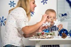 Vrolijke Kerstmis en gelukkige vakantie! Moeder en zoon die een sneeuwvlok schilderen De familie creeert decoratie voor Kerstmisb stock afbeelding