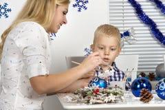 Vrolijke Kerstmis en gelukkige vakantie! Moeder en zoon die een sneeuwvlok schilderen De familie creeert decoratie voor Kerstmisb royalty-vrije stock foto's