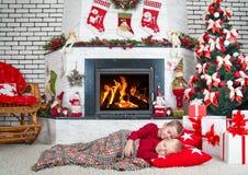 Vrolijke Kerstmis en Gelukkige Vakantie! Twee broersslaap in de woonkamer op de vloer onder de boom In afwachting van giften van stock foto