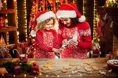 Vrolijke Kerstmis en gelukkige vakantie Vrolijk leuk krullend meisje en haar oudere zuster in santashoeden het koken stock afbeeldingen