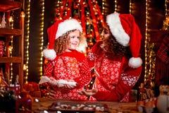 Vrolijke Kerstmis en gelukkige vakantie Vrolijk leuk krullend meisje en haar oudere zuster in santashoeden het koken stock foto's