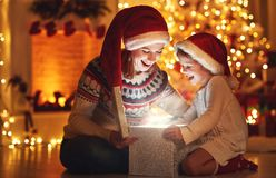 Vrolijke Kerstmis! familiemoeder en kind met magische gift bij ho stock fotografie