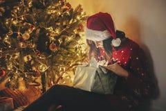 Vrolijke Kerstmis gelukkig meisje die in santahoed magische Kerstmis openen royalty-vrije stock fotografie