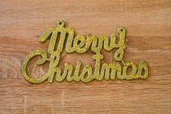 Vrolijke Kerstmis gouden tekst op een houten achtergrond royalty-vrije stock foto's
