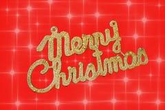 Vrolijke Kerstmis gouden tekst op een rode achtergrond met sterren stock afbeelding