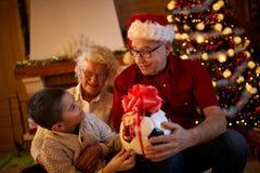Vrolijke Kerstmis - het glimlachen de gift van de familieholding Stock Foto's