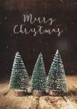 Vrolijke Kerstmis met Kerstmisboom en sneeuw die op grunge houten t vallen stock fotografie
