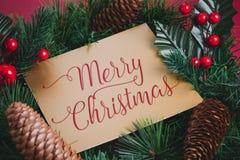 Vrolijke Kerstmis op gouden groetkaart op Groene kroon met pijnboom stock afbeeldingen