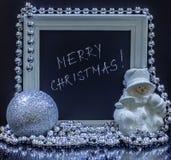 Vrolijke Kerstmistekst in een wit houten kader met een sneeuwman, sil stock foto