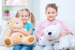 Vrolijke kleine zusters die op de bank zitten Royalty-vrije Stock Foto's
