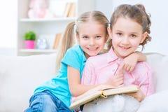 Vrolijke kleine zusters die op de bank zitten Stock Fotografie